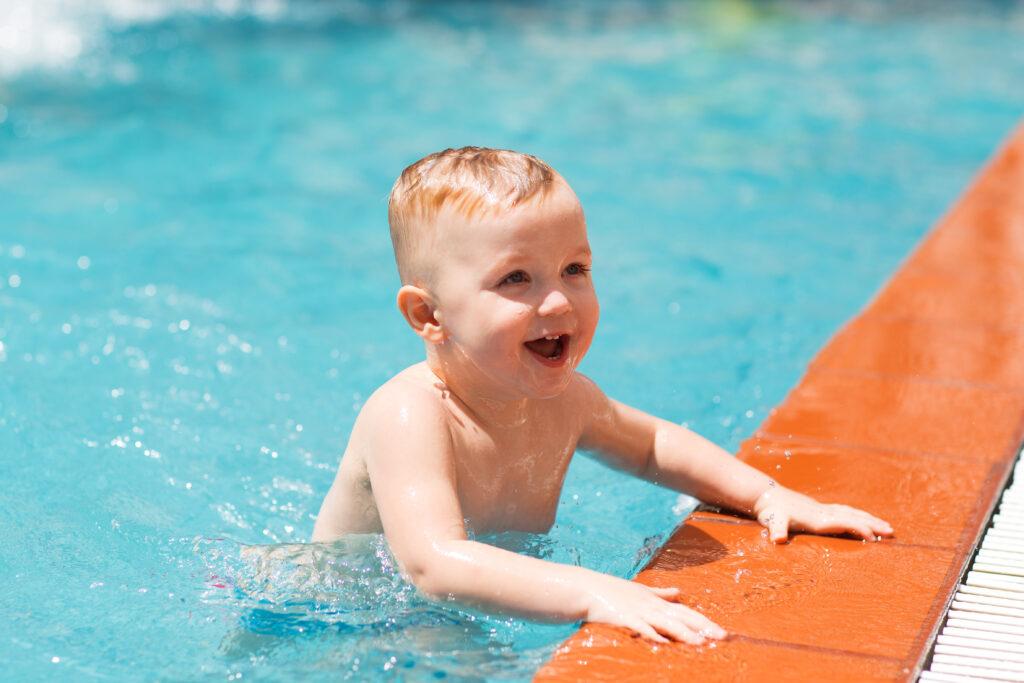 portrait happy little boy swimming pool